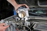 Car mechanic repairing a part of engine.