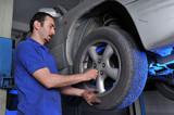 Autószerelő eltávolítása kerékanyáknak változtatni gumik.