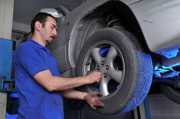 Car mechanic removing wheel nuts to change tires.