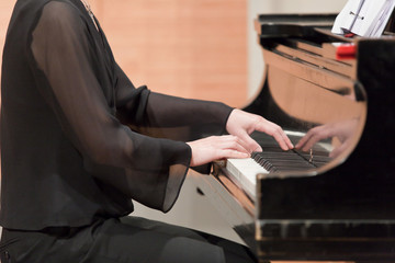 Hands of piano player during performance.