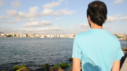 man with blue t shirt waiting by sea side