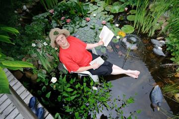 Frau sitzt mit Büchern im Biotop