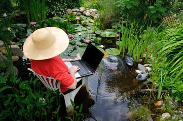 Frau sitzt mit Notebook im Biotop zwischen Seerosen