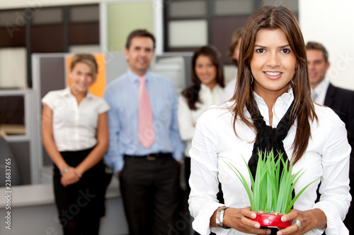 Business woman holding a plant