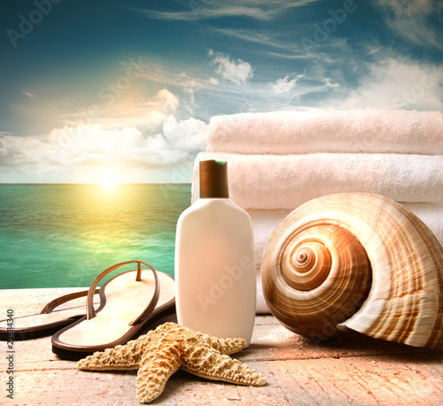 Sunblock lotion and towels and ocean scene - 23684340