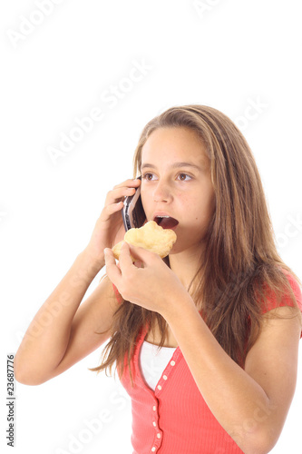 teen eating a cookie while talking on cellphone