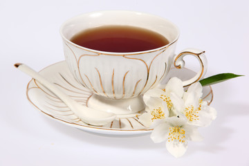 Cup of tea with jasmine flowers isolated on white.