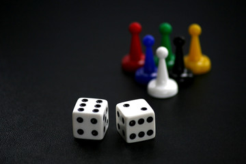Dice and game pieces on black
