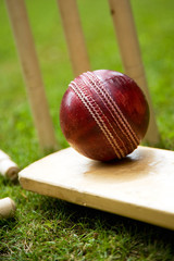 Red leather cricket ball on grass with stumps
