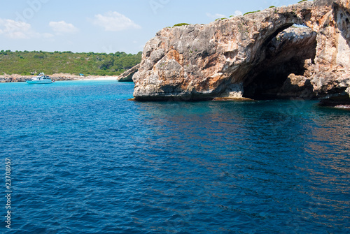 Natural arch and recreational boat at Cala Antena, Majorca, Spai