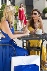 Two Beautiful Young Women Having Coffee With Shopping Bags
