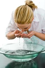 eine hübsche junge Frau wäscht sich das Gesicht