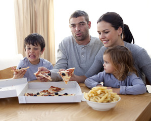 Cheerful young family eating a pizza in the living-room