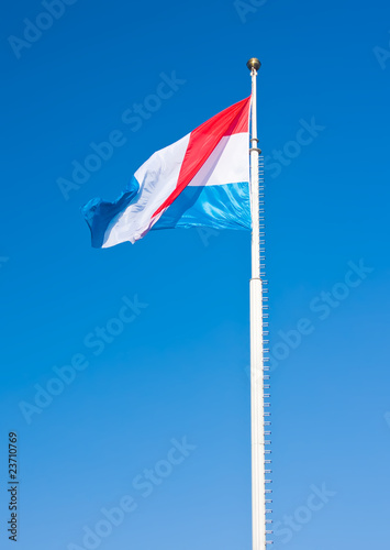 Flag of Luxembourg over blue sky