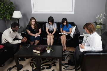 A Group Of People With Their Bibles Praying Together