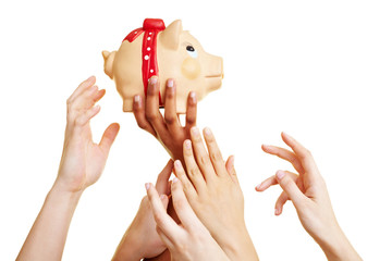 Hände greifen nach einem Sparschwein