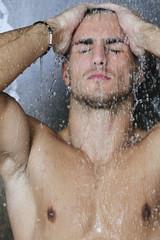 good looking man under man shower