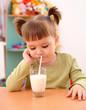Gloomy little girl drinks milk