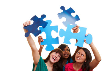 Drei Frauen halten Puzzleteile