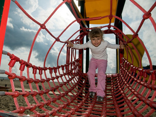 Little girl playing on a jungle gym