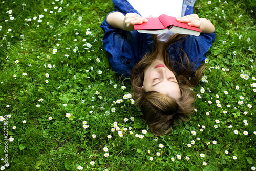 Woman lying on grass, reading book - 23735350