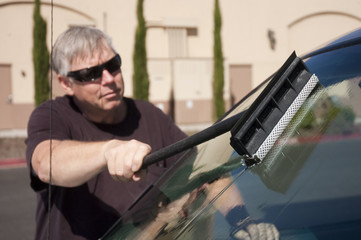man cleaning windshield