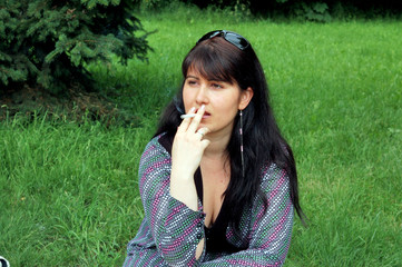 Portrait of young woman smoking cigarette outdoors