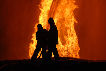 two firemen battling against raging fire