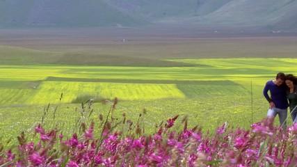 Coppia cammina tra campi fioriti