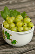 Bowl of freshly picked gooseberries on wooden table