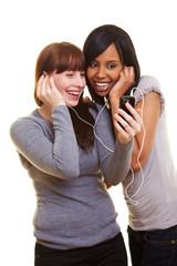 Zwei Frauen hören Musik mit einem Handy