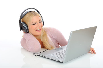 young girl listen and sing to the music with headphones, laptop