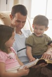 A Father Reading The Bible To His Young Son And Daughter