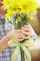 A Boy Holding A Bouquet Of Yellow Daisies