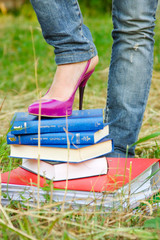 a leg of young beautiful girl with books and folder on nature