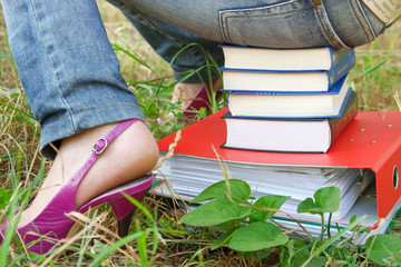 leg and buttocks of  girl sitting on the books and folder