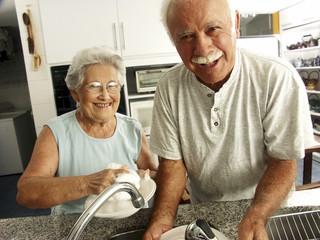 Abuelos lavando platos.