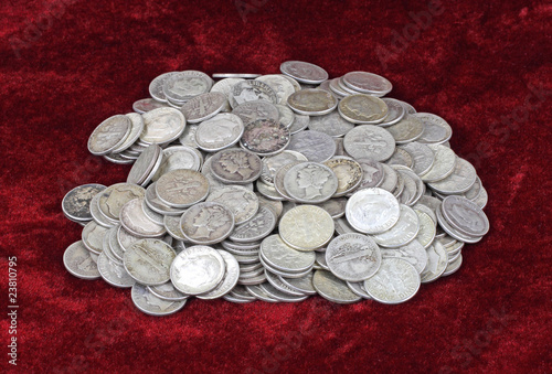 Old silver dimes on a red velvet cloth background