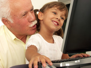 Abuelo y nieta en una computadora.