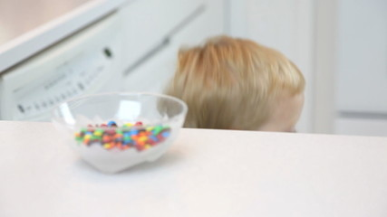 Young Boy Sneaking Candy out of Candy Bowl