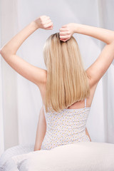 Blond hair woman stretching arms above head in bedroom