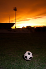 football on the ground with sunset