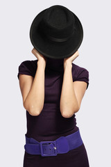 girl gracefully hides her face behind a hat