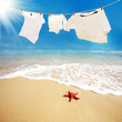 white T shirts hung on a line  on beach