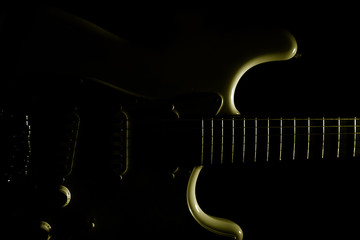 Electric guitar is dramatic light, on black