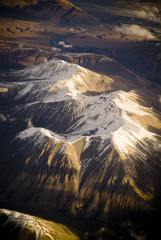 Aerial view of mountain range with snow capped peaks