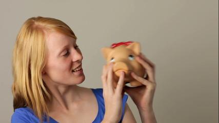 Woman shaking piggy bank