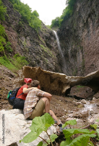couple in front of the waterfall in alps