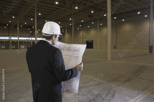 Man studies blueprint in empty warehouse