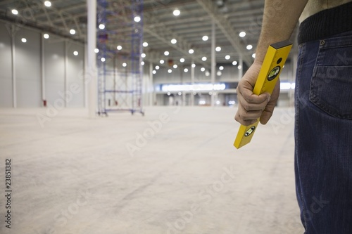 Man stands holding spirit level in empty warehouse